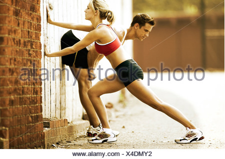 Man and woman runner stretching - Stock Photo