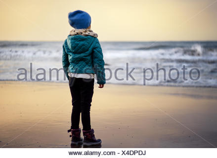 Girl (2-3) looking at beach at sunset - Stock Photo