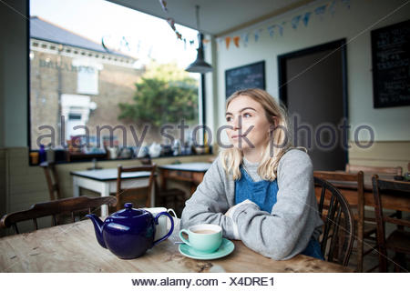 Young woman sitting in cafe, cup of tea and teapot on table, thoughtful expression - Stock Photo