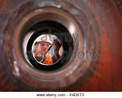 Engineer working on excavator parts in surface coal mine - Stock Photo