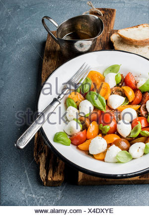 Italian Caprese salad with cherry tomatoes, small mozzarella and fresh basil in white enamel plate on rustic wooden board over g - Stock Photo