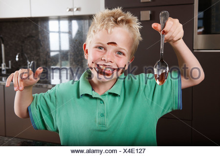 Boy in kitchen with cake mix on his face - Stock Photo