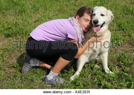 Ein Kind schmust mit einem Hund - Stock Photo