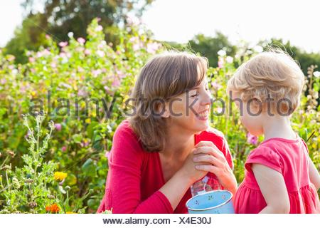 Mid adult mother and toddler daughter in flower field - Stock Photo