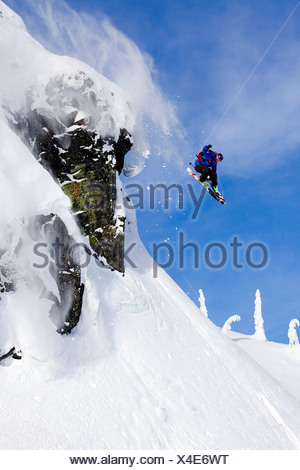 Man skiing over a rock cliff in the Whistler backcountry, Coast Mountains, British Columbia, Canada. - Stock Photo