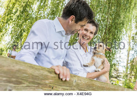 Portrait of couple with pet dog, standing by fence in forest - Stock Photo