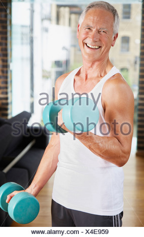 Man lifting dumbbells in living room - Stock Photo