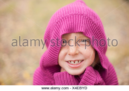 A girl in a magenta hooded sweater, with the hood covering her head - Stock Photo