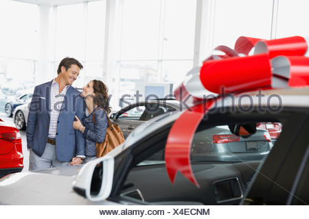 Couple hugging in car dealership showroom - Stock Photo