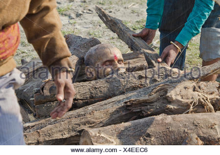Putting a dead body on firewood on the banks of river Yamuna as part of a cremation ceremony, Vrindavan, India, Asia - Stock Photo