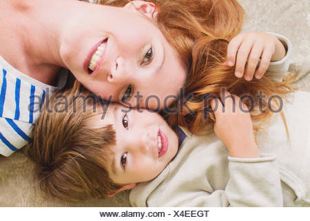 Overhead view of a happy mother and son lying on floor - Stock Photo
