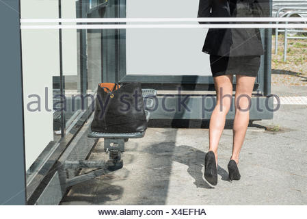 Businesswoman Walking Forward With Handbag Left On Bench - Stock Photo