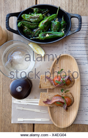 Crisp bread with herrings and tomatoes,grilled green peppers - Stock Photo
