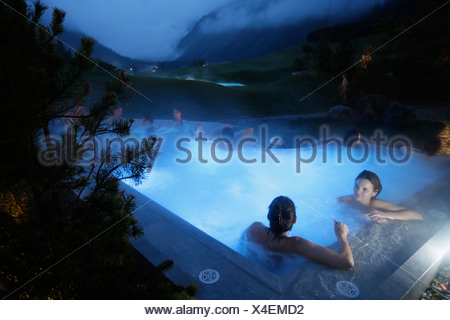 Hotel guests bathing in an outdoor saltwater bath, Tannheim, Tannheim Valley, Tyrol, Austria - Stock Photo