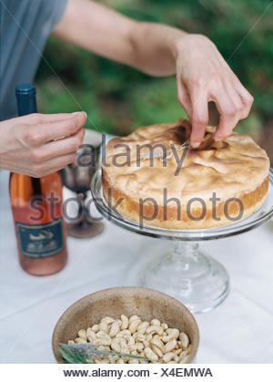 A woman decorating a cake on a glass stand. A dish of nuts and a bottle of rose wine. - Stock Photo