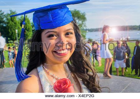 Portrait of teenage girl wearing graduation cap - Stock Photo