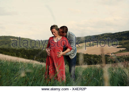 Romantic man with hands on pregnant wife's stomach in landscape - Stock Photo