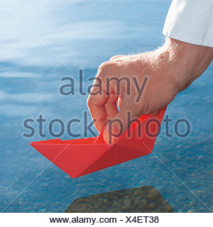Germany, Human hand holding red origami boat - Stock Photo