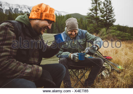 Smiling male hunter friends drinking coffee outside tent at campsite in remote field - Stock Photo