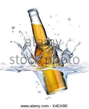 Clear Beer bottle falling into water, forming a crown splash. Viewed from a side close up, with also the part under water visible. On white - Stock Photo