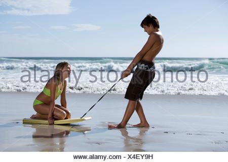 Teenage couple 13 15 playing on beach boy pulling girl along sand on bodyboard profile - Stock Photo