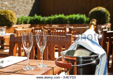 Champagne bottle in ice bucket with glasses - Stock Photo
