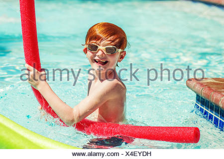 Young boy (6-7) playing in swimming pool - Stock Photo