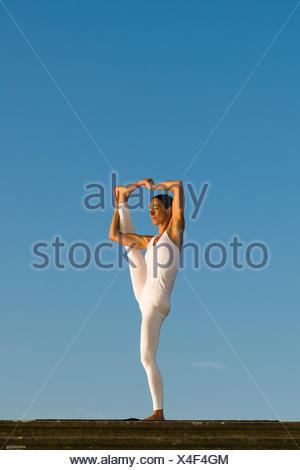 Young woman practising Hatha yoga, outdoors, showing the pose Utthita Hasta Pandangusthasana, raised hand to big toe pose - Stock Photo