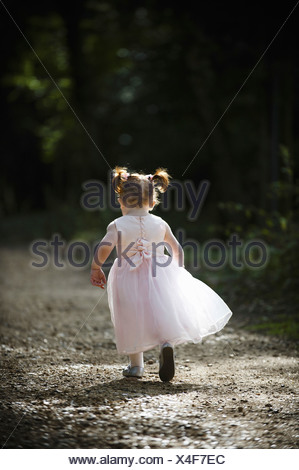 child running away from camera floaty special pink bridesmaid dress red hair pigtails - Stock Photo