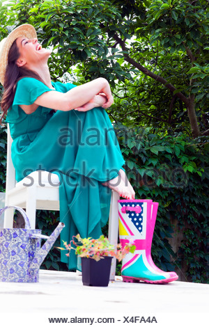 Young woman wearing green dress sitting on chair laughing - Stock Photo
