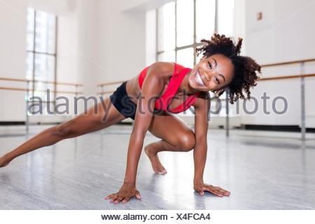 Young woman in dance studio resting on hands, leg outstretched looking at camera smiling - Stock Photo