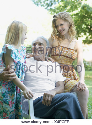 Senior man with woman and young girl sitting outdoors smiling - Stock Photo