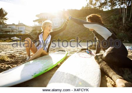 Couple sitting on beach, clapping hands in high five, surfboards beside them - Stock Photo