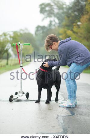 Girl stroking dog tied to push scooter - Stock Photo