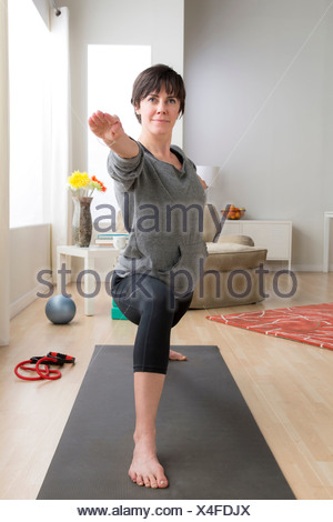 Mid adult woman doing yoga at home - Stock Photo