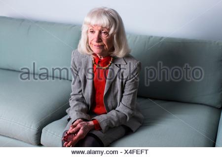 Senior woman sitting on sofa with blank expression - Stock Photo