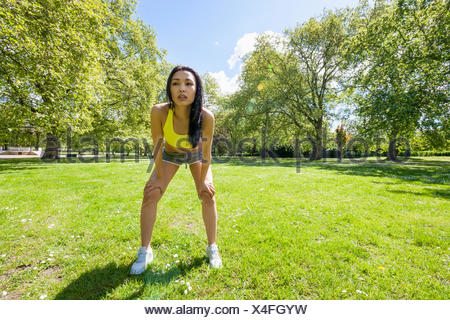 Full length of tired fit woman taking a break while exercising in park - Stock Photo