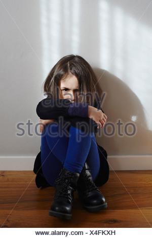 Portrait of stubborn young girl sitting on floor hugging knees - Stock Photo