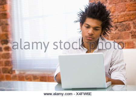 Businessman in office typing on laptop - Stock Photo