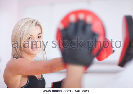 Young woman boxing in gym - Stock Photo