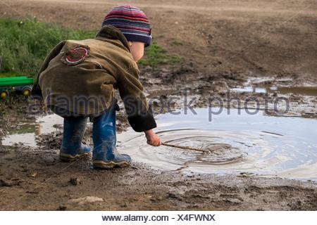 Male toddler wearing rubber boots playing with stick in puddle - Stock Photo