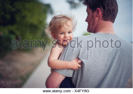 Father carrying smiling son - Stock Photo