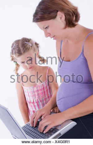 pregnant young woman working on the laptop in her lap, young daughter standing beside watching - Stock Photo