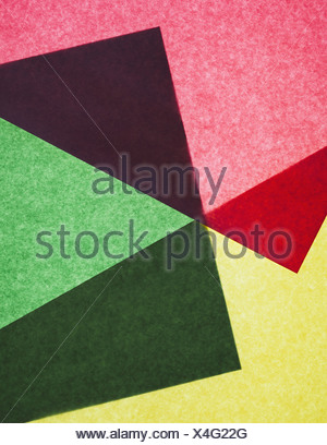 Pieces of colourful, recycled construction paper, overlapping and laid out at random. - Stock Photo