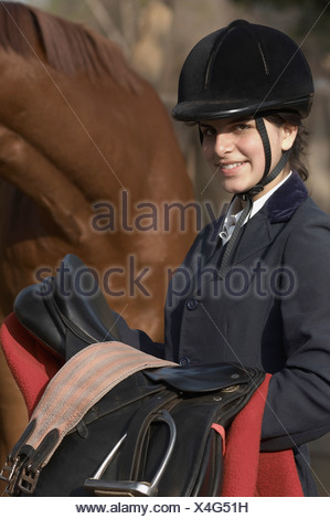 Portrait of a female jockey standing with a horse and smiling - Stock Photo
