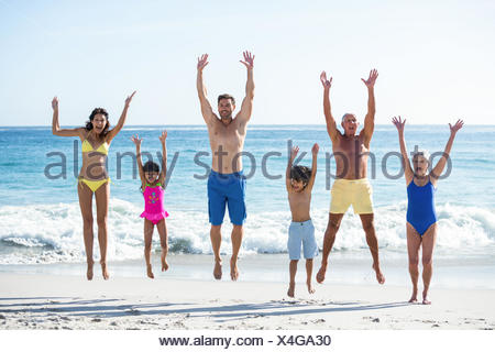 Happy family jumping on the beach - Stock Photo