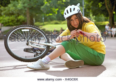 Young woman injured and clutching arm - Stock Photo