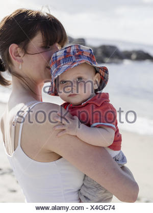 Mother holding her baby son. - Stock Photo
