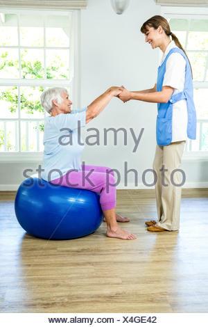 Smilnig nurse assisting senior woman - Stock Photo