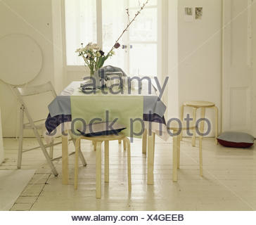 Contemporary decoration of dining room in traditional flat with white painted floorboards - Stock Photo